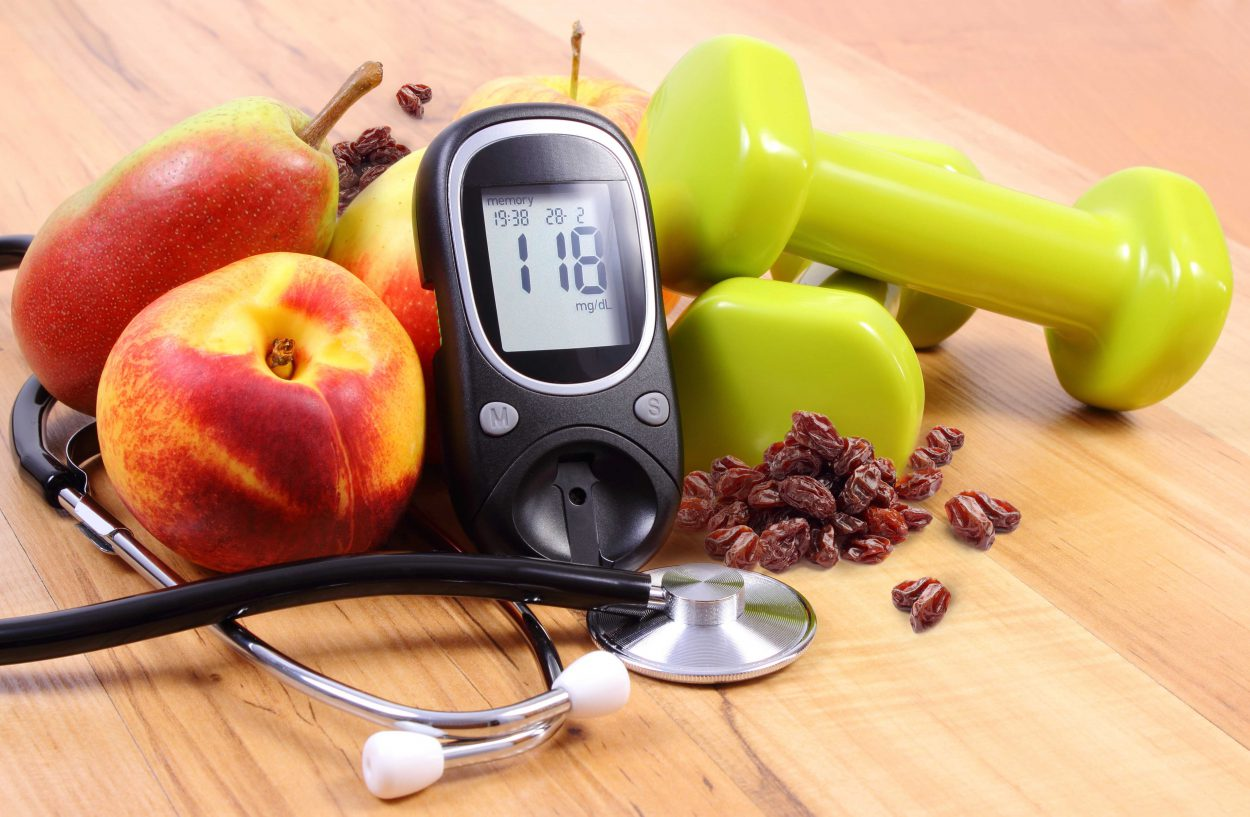 Glucose meter with medical stethoscope, fruits and dumbbells for fitness